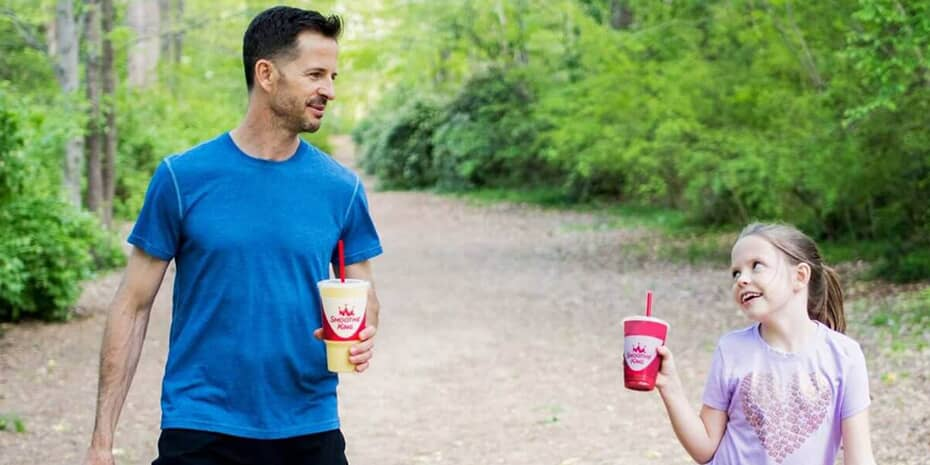 Dad and daughter on hike drinking smoothies from Smoothie King