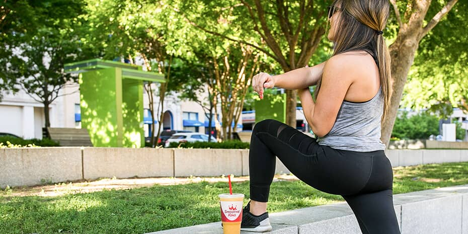 Girl stretching in park while drinking a Smoothie King smoothie
