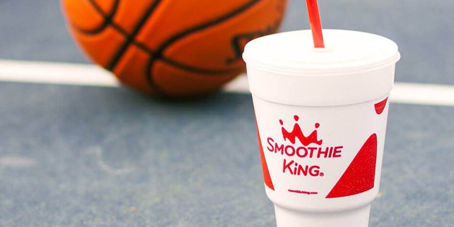 person holding basketball behind smoothie king cup