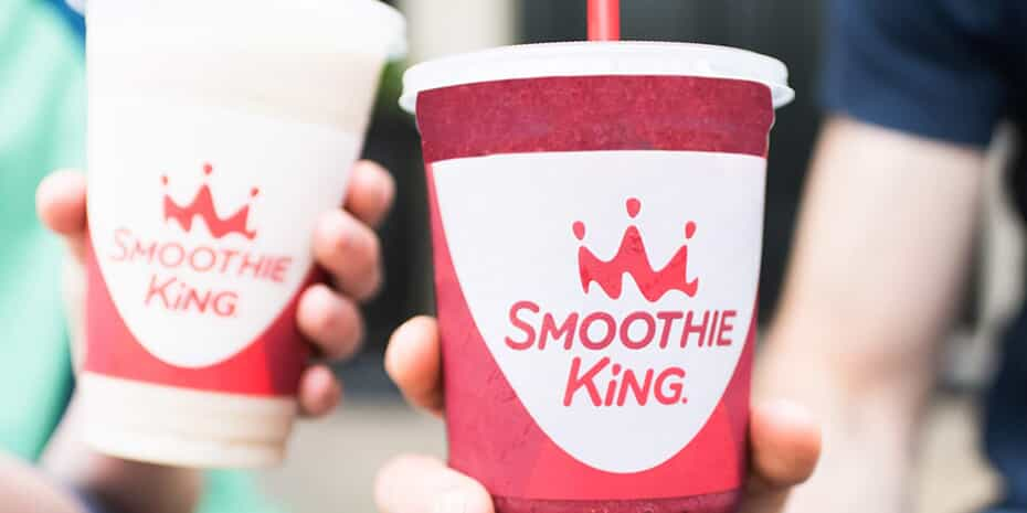 two smoothie king cups being held