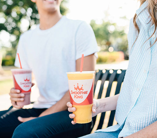 Two people sitting on a bench holding Smoothie King smoothies
