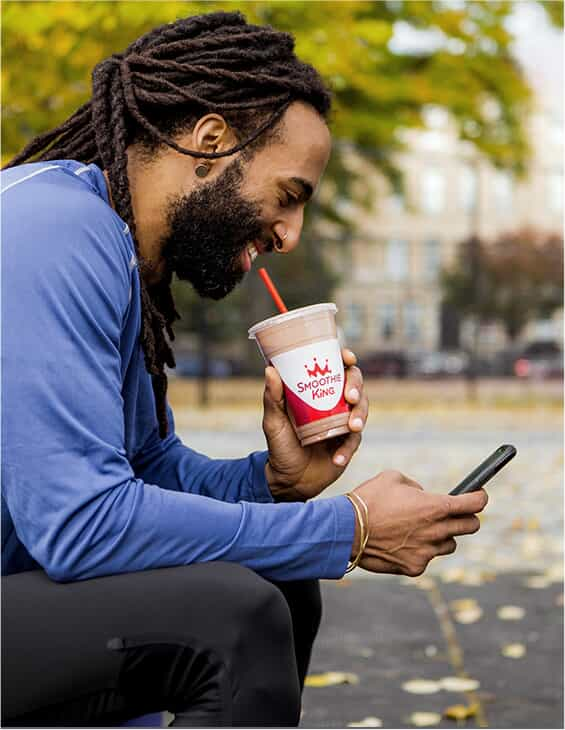 Guy drinking Smoothie King Smoothie on his cell phone