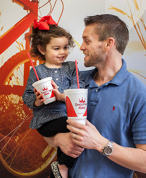 Owner holding his daughter smiling holding Smoothie King Smoothies